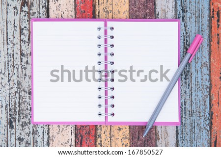 Open purple notebook and pen on vintage wood table for background and text