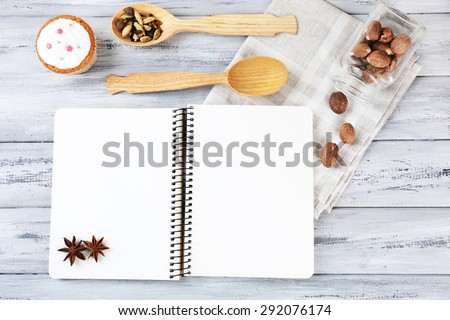 Open recipe book and tasty bakery on wooden background - stock photo