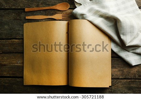Open recipe book on wooden background - stock photo