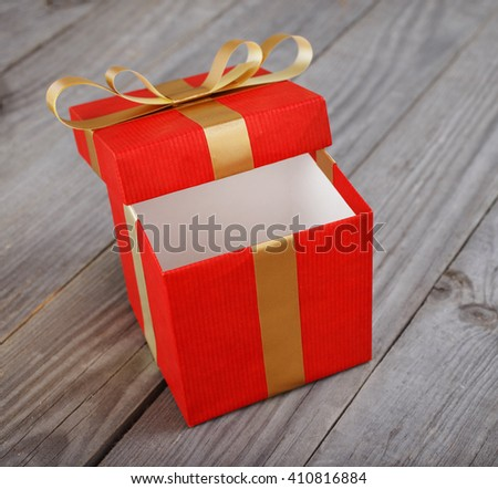 open red gift box with gold ribbon on the wooden table close up - stock photo