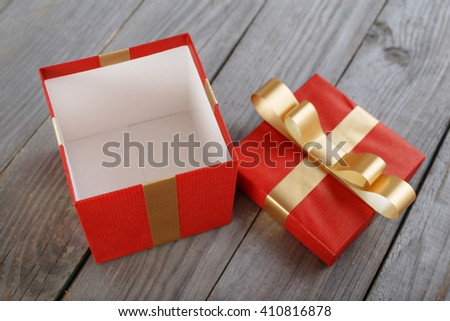 open red gift box with gold ribbon on the wooden table, top view - stock photo
