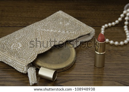 Open red lipstick by 1920s purse with vintage powder compact on antique oak dressing table.