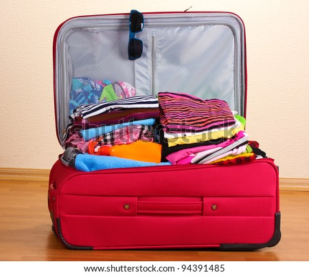 Open red suitcase with clothing in the room - stock photo