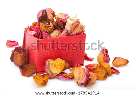 Open red treasure box with red withered petals of rose on white - stock photo