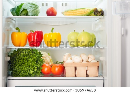 Open refrigerator full of fruits and vegetables. Weight loss diet concept. - stock photo