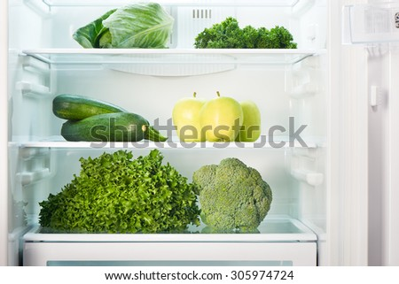 Open refrigerator full of green fruits and vegetables. Weight loss diet concept. - stock photo