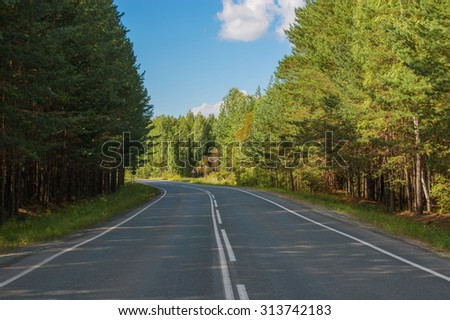 Open Road in future, no cars, auto on asphalt road through green forest, trees, pines, spruces. Clouds on blue sky in summer, sunshine, sunny day. Good weather. bokeh, blurred road vintage photo image