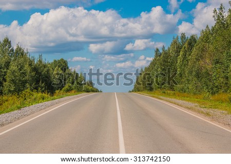 Open Road in the future, no cars, auto on asphalt road through dark green forest, tree and yellow field and clouds on blue sky in summer and sunshine, sunny day. Good weather. Photo, image background. - stock photo