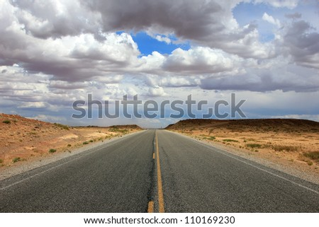 Open road in the Utah desert with beautiful sky. - stock photo