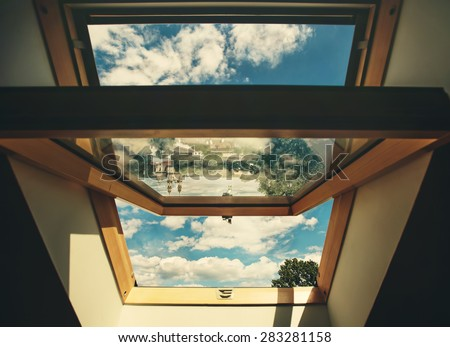 Open roof window skylight with old European city reflection, the chapel and cloud sky - stock photo