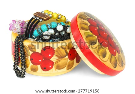 Open round wooden box with lid in the folk style with jewelry isolated on a white background.