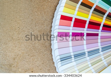 open sample colors catalogue on wood background - stock photo