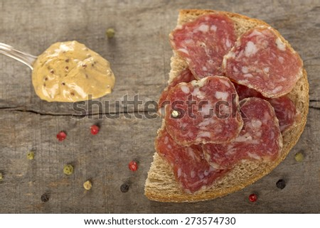 Open sandwich of salami slices on whole grain bread and spoon with mustard - stock photo