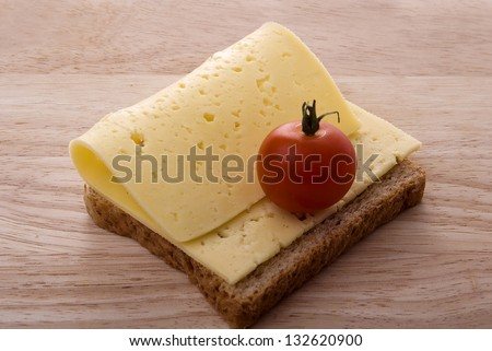 open sandwich with cheese and cherry tomato on a wooden cutting board - stock photo
