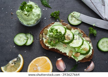 Open sandwich with ricotta, fresh herbs and cucumber. View from above. - stock photo