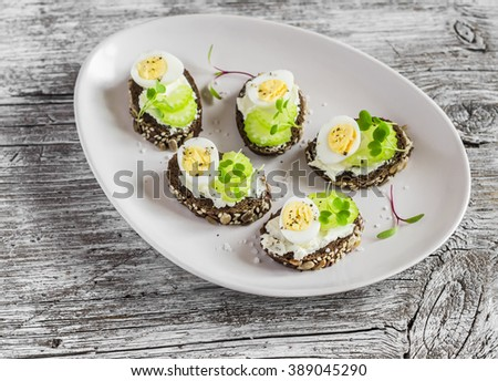 Open sandwiches with cream cheese, quail eggs and celery. Delicious healthy Easter snack or breakfast - stock photo