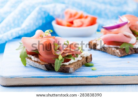 Open sandwiches with ham, tomato and arugula over blue background, selective focus - stock photo