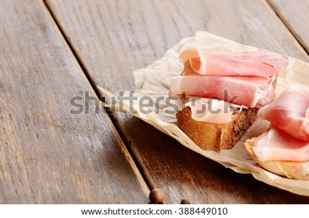 Open sandwiches with jamon on wooden table