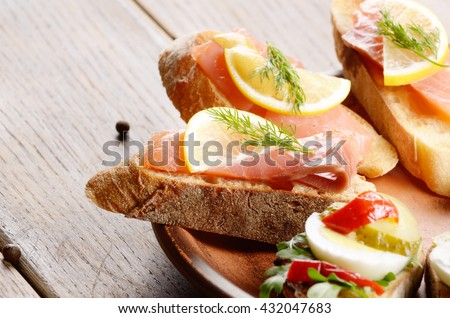 Open sandwiches with salmon on ceramic plate
