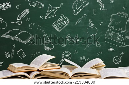 Open school books with written sketches on school table  - stock photo