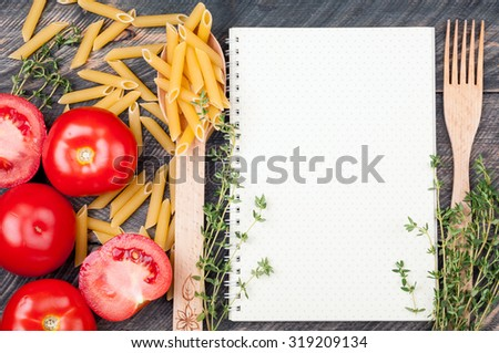 Open sheet cookbook with pattern polka dot, spoon with penne pasta, tomatoes, thyme on old wooden background. Ingredients for cooking. Open blank recipe book. Top view - stock photo