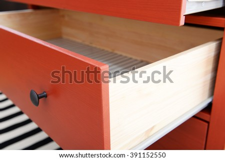 Open shelf of chest of drawers closeup - stock photo