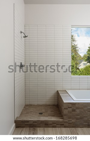 Open shower and bath in a modern home. Shower is lined with white tile and marble, with a view window. Also seen is the wooden floor, and a view to a neighboring house. - stock photo