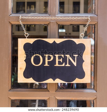 open sign hanging on deluxe door at store - stock photo