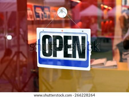 Open sign in street cafe business sign shot through a dirty diner window  - stock photo