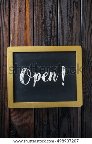 Open Sign Written In Chalk On Chalkboard On Rustic Vintage Wood Background. Top View Selective Focus.