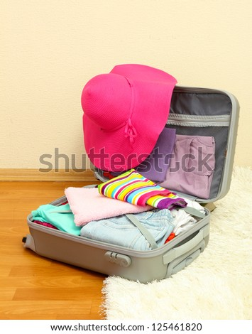 Open silver suitcase with clothing in room