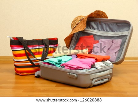 Open silver suitcase with clothing in room - stock photo
