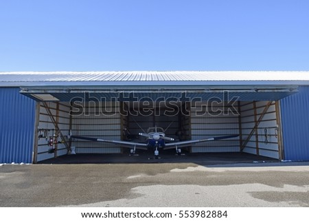 open small aircraft hangar with propeller plane parked inside