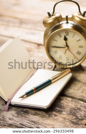 Open small notebook with retro-fashioned fountain pen and alarm clock behind. Writing vintage background - stock photo