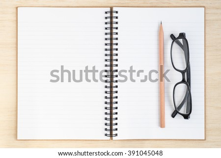 Open spiral notebook, empty line paper with brown pencil and black glasses - notebook paper on wood background - working desk top view - stock photo
