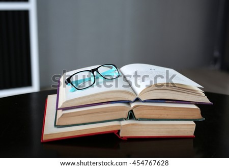 Open stack hardback books with glasses on wooden table. Education background. - stock photo