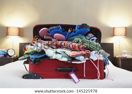 Open suitcase on bed - stock photo