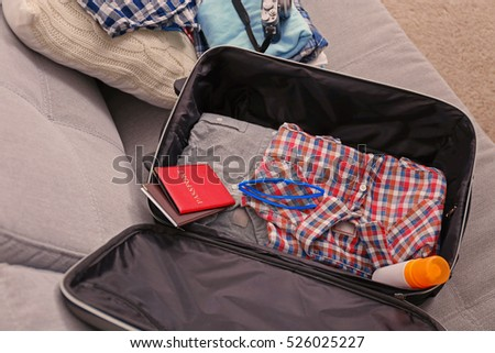 Open suitcase with clothes and personal things on sofa