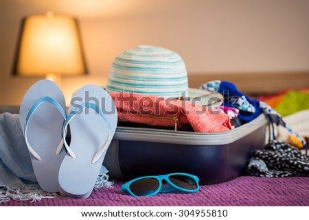 Open suitcase with clothing in the bedroom. Summer holiday concept. - stock photo