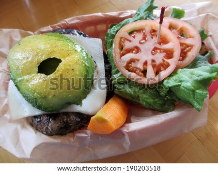 Open Swiss Cheese Hamburger with Veggies of Avocado, Lettuce, tomateos and Carrots in a red plastic basket on a table. - stock photo