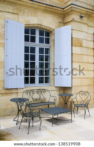 Open terrace with iron patio furniture and blue window shutters on the background, Gironde, France