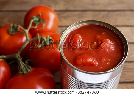 Open tin of chopped tomatoes with whole fresh unfocused tomatoes behind. Wood surface.