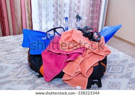 Open travel bag with flippers on bed closeup - stock photo