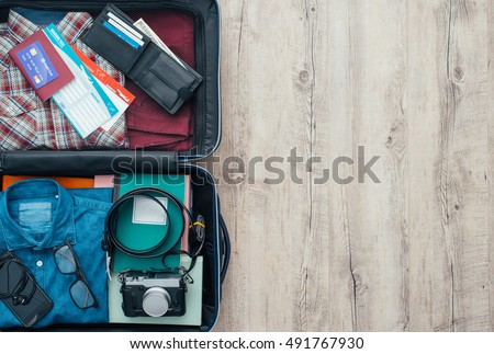 Open traveler's bag with clothing, accessories, credit card, tickets and passport, travel and vacations concept, flat lay