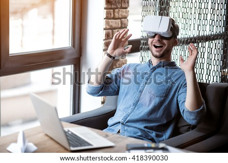 Open up  a new world. Overjoyed smiling handsome man sitting at the table and expressing gladness while using virtual reality device  - stock photo