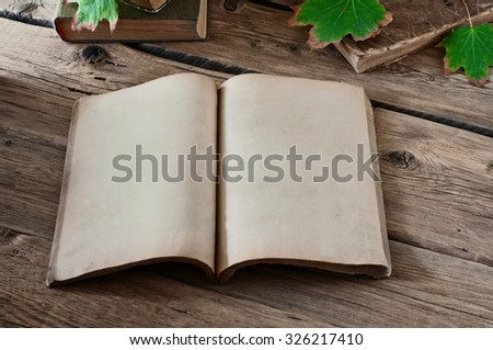 Open vintage book with blank pages on wooden table with autumn maple leaves close-up. Copy space. Free space for test - stock photo