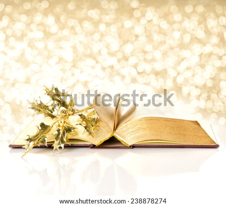 open vintage book with golden pages. bible with golden decoration. shiny lights christmas background - stock photo