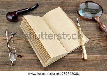 Open Vintage Notebook With Blank Pages, Gold Fountain Pen, Glasses, Retro Magnifier, Compass and Smoking Pipe On Grunge Wooden Table Background - stock photo