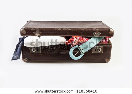 Open vintage suitcase clothing on a white background