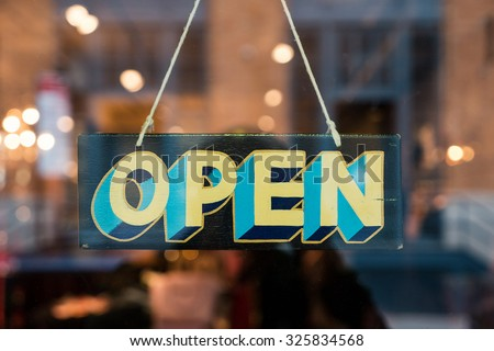 Open vintage wooden sign broad through the glass of store window. Filtered image. - stock photo